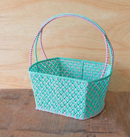 Beautiful plastic basket on wooden background