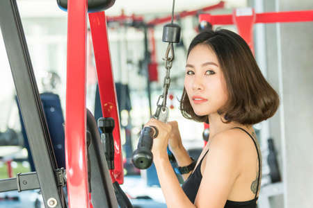 Asian women exercising building muscles at fitness club Stock Photo