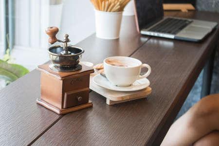 カフェでテーブルの上のコーヒー カップとコーヒー グラインダー 写真素材
