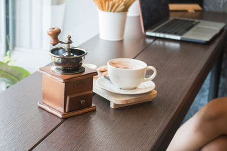 Coffee grinder with coffee cup on table in cafe Stock fotó