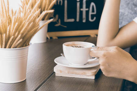woman hands with latte on a wood table,food background Stock Photo