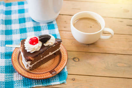 Slice chocolate cake with hot coffee on wooden table