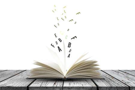 Open boek met vliegende letters op houten planken op witte achtergrond, onderwijs en boekconcept