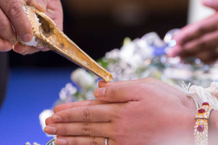 Thai traditional wedding ceremony, water-pouring ceremony on brides hands