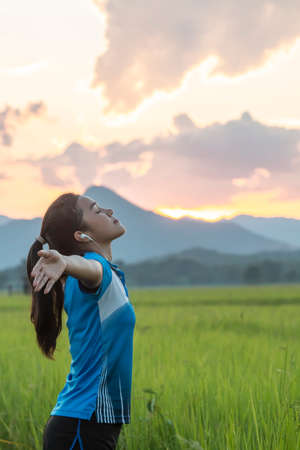 Young asian woman enjoying spring breeze in rice field with sunset