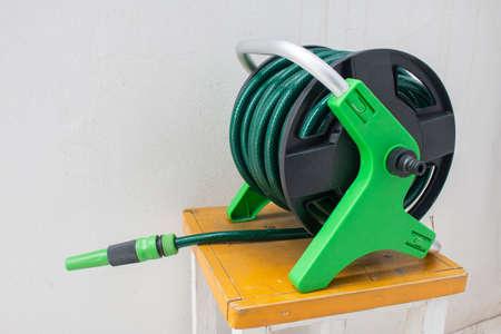 Buse de tuyau d'arrosage de jardinage sur fond de béton