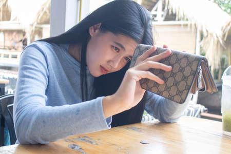 arme asiatische frau offene leere geldbörse auf der suche nach geld mit zahlungs- oder schuldenproblemen, Standard-Bild