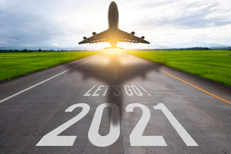 The word let's go written and 2021 and air plane on highway road in the middle of empty asphalt road 스톡 콘텐츠