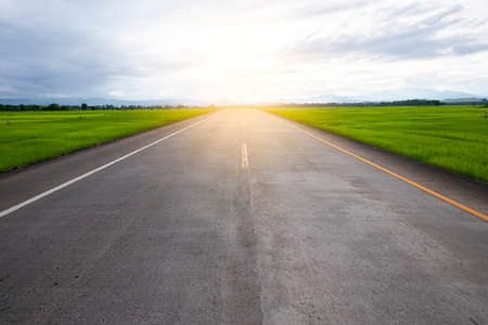 Empty asphalt road through the green field and clouds on blue sky