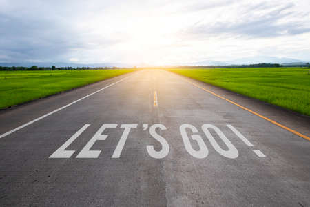 The word let's go written on highway road in the middle of empty asphalt road