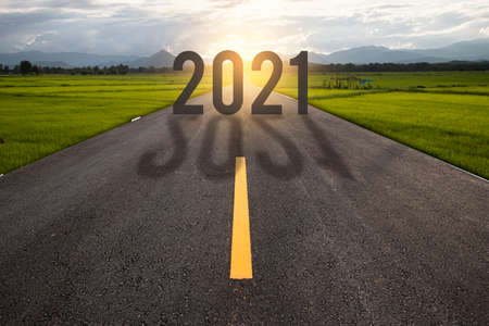 The word 2021 written on highway road in the middle of empty asphalt road at golden sunset 스톡 콘텐츠