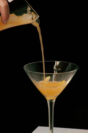 pouring cocktail with a twist of lemon in the glass Imagens