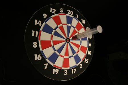 dart board with syringe in the center