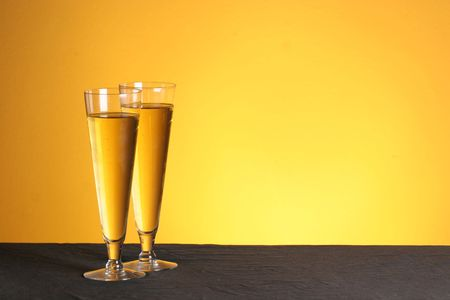 two pilsner glasses on a golden backdrop with copy space