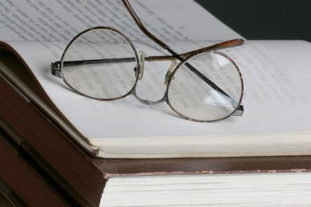 eye glasses set on top of a open page photo