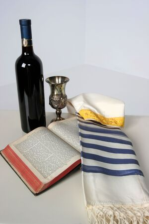 Holy Scriptures opened with Talid resting on it Kaddish cup and a bottle of red wine Imagens