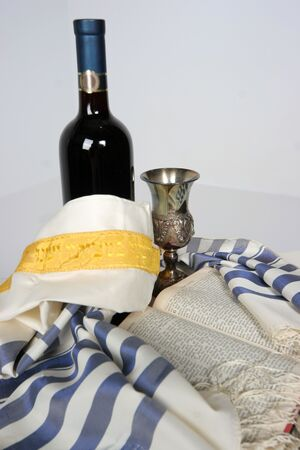 yom kippur: Holy Scriptures opened with Talid resting on it Kaddish cup and a bottle of red wine Stock Photo