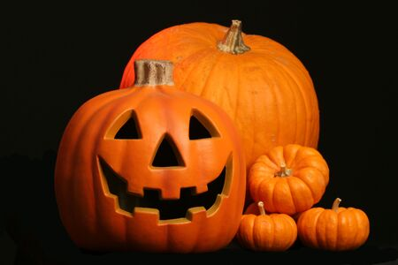 seasonal harvest of squash and a Halloween face carved in a jack o lantern Imagens - 253711
