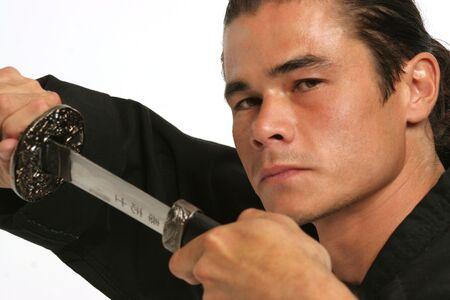 scheide: attraktiver Kerl schaut �ber seiner Samuraiklinge, wie er sie von der Scheide entfernt