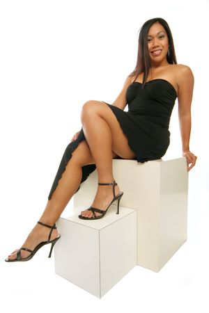 beautiful Philippine girl kicks back on boxes in black dress isolated on white