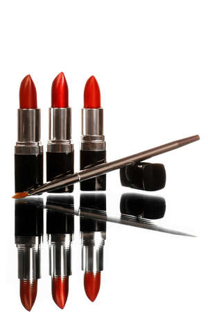 three lipsticks on white with lip brush and reflection shot vertical Stock Photo
