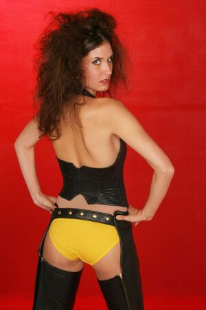 fascinate: girl in leathers and yellow undies is busting out her bottom on red set Stock Photo