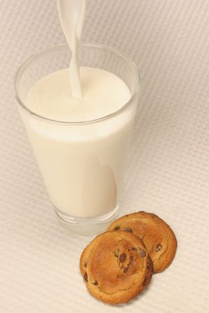 pouring a glass of milk and cookies Imagens