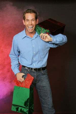 guy goes shopping for the holiday gifts on red foggy backdrop Imagens