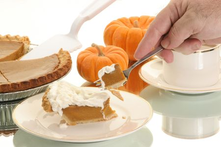 hand takes a piece of pumpkin pie ready to eat it photo