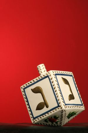 clay chanukkah dreidel on red background