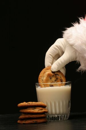 santa dips a cookie in the milk with pile of chocolate chip cookies on black background