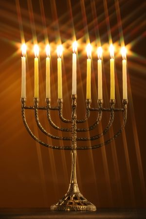 different perspective on a traditional Hanukkah menorah with all candle lite with star filter on a gold background Imagens