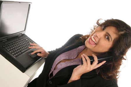 woman talking over the phone and typing on her computer