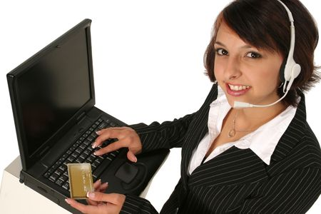 woman holding her credit card while placing an order on her computer