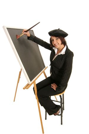 artist starting with a blank canvas on an easel as she prepares to create Stock Photo