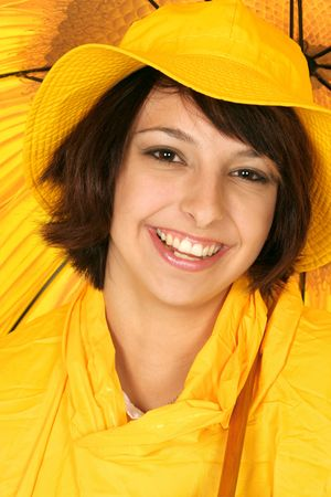 girl smiles in her bright yellow rain gear and umbrella