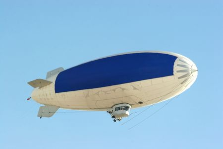 drifts: blimp flying in clear blue sky with blue copy space to advertise your message Stock Photo