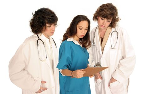 three women medical professionals looking over report Imagens