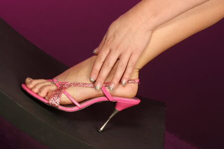 beautiful pink shoe on foot with hand wrapped at her ankle fingers well manicured Stock Photo