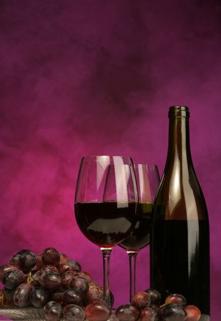 Vertical of Wine bottle with glasses and grapes on purple background