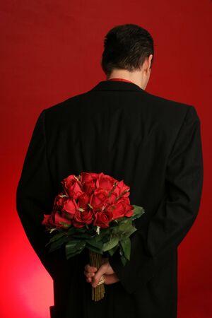 suitor: uomo di grande azienda mazzo di rose rosse dietro la schiena su sfondo rosso  Archivio Fotografico
