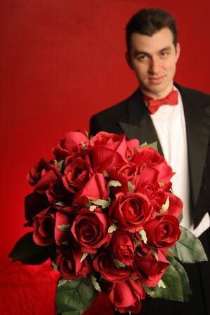 suitor: equipaggi la tenuta verso lesterno il grande mazzo delle rose rosse nel tux nero convenzionale con il legame di arco rosso