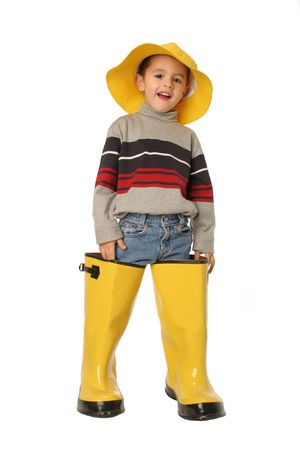 rain boots: Wading in Dads shoes this young boy standing in large yellow rain boots and a yellow rain hat isolated on white Stock Photo