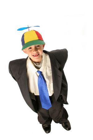 young boy in very large suit cap with blue propeller blade and saying I dont want to grow up missing his two front teeth isolated on white Imagens