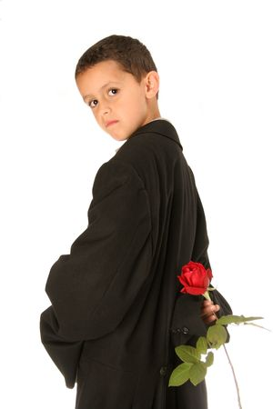 timeless expression of this sweet young man with a red rose bud isolated on white in dads tuxedo
