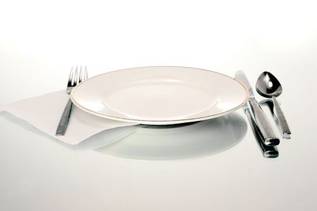 white plate with silverware and a napkin