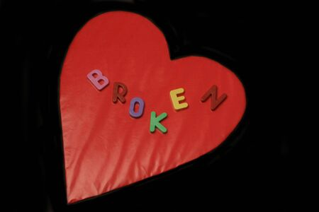 broken spelled out on red heart with black background