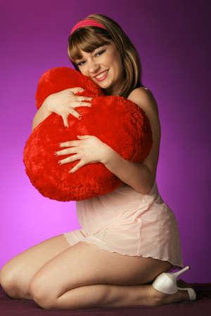 nighty: pretty girl holds soft heart near on purple backdrop Stock Photo