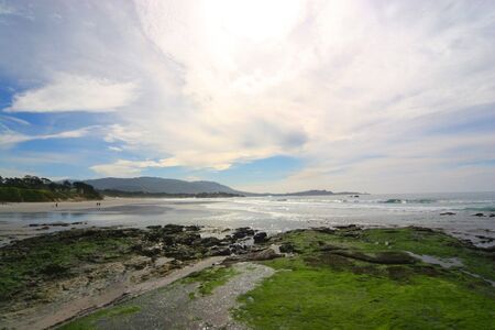 picturesque wide view of pebble beach coast line with wind swept clouds in a blue sky Imagens