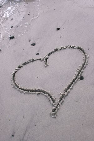 vertical of heart drawn in the sand Imagens